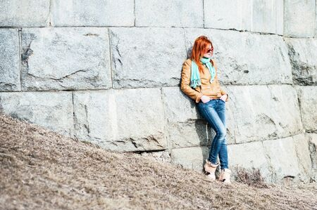 to lean: Nice red-haired girl in sunglasses lean on stone wall.
