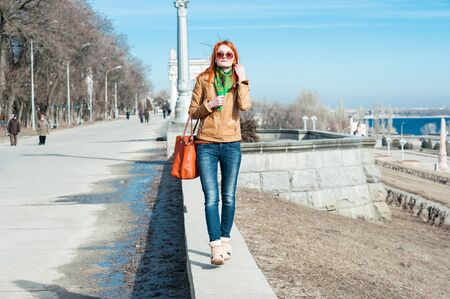 redhaired: Nice red-haired girl in sunglasses walking outdoors. Stock Photo