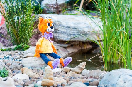 soft toy: Soft toy - orange cat sitting on the stone