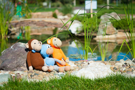 soft toys: Soft toys - three monkeys sitting in park Stock Photo