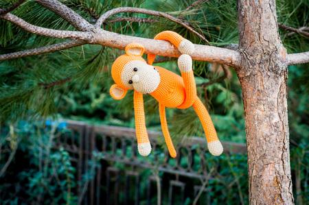 soft toy: Soft toy - orange monkey climb on the tree