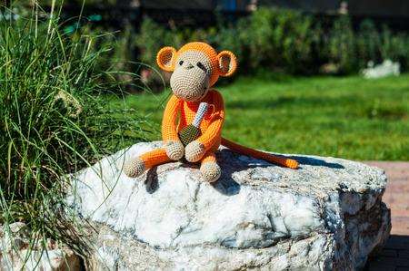 soft toy: Soft toy - orange monkey with grenade sitting on stone