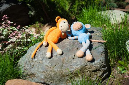 soft toys: Soft toys - two toy monkeys lying on the stone Stock Photo
