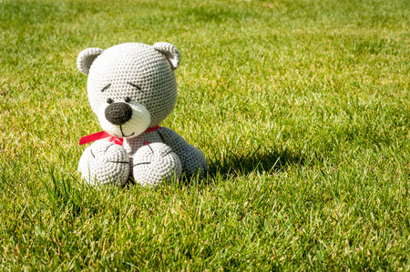 soft toy: Soft toy - grey bear sitting on the grass Stock Photo