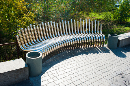 unorthodox: Unusual metal pipe bench on pavement, summer day