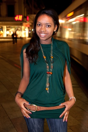 Portrait of young african american woman in city at night. photo