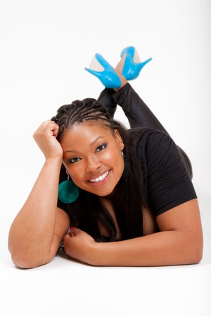Portrait of a young beautiful black woman lied on the floor and smiling photo