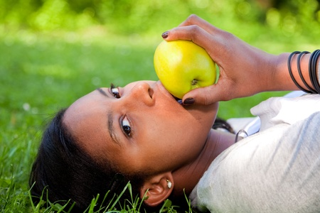 Beautiful black woman laying down outside on grass  eating an apple