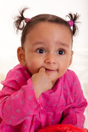 mixed races: Beautiful mixed race baby girl with his finger in the mouth Stock Photo