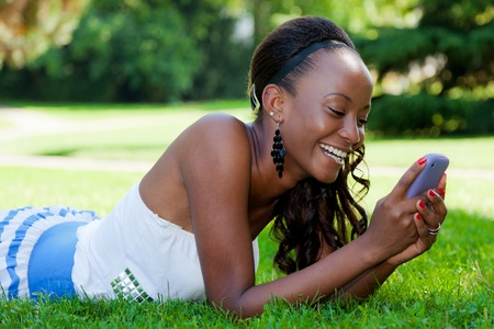Smiling teenage black girl using a phone, lying on the grass photo