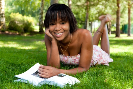 student reading: Outdoor portrait of young african american woman lying down on the grass reading a book Stock Photo