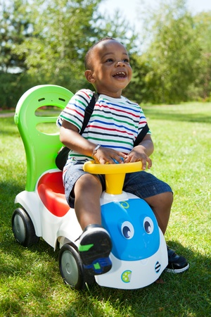 children playing outside: Cute little african american baby boy playing at park
