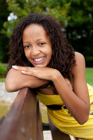 Portrait of a young beautiful african american woman sitting on a bench Stock Photo - 10394540