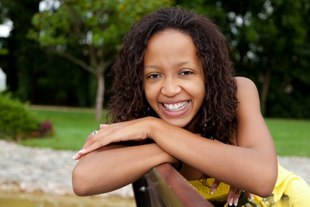african ethnicity: Portrait of a young beautiful african american woman sitting on a bench Stock Photo