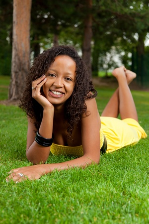 mixed ethnicities: Young beautiful african american woman lying down on the grass
