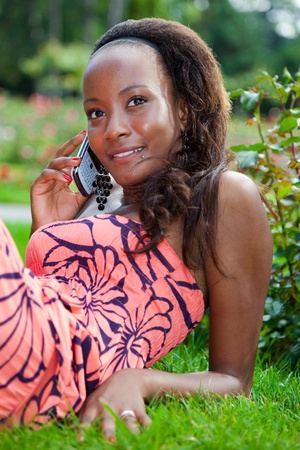 feminine beauty: Smiling teenage black girl using a phone, lying on the grass