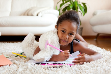 Little African Asian girl  drawing, lying on the floor Stock Photo - 10677744