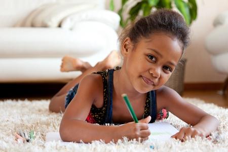 niños africanos: Niña Africana asiática dibujo, acostado en el piso Foto de archivo