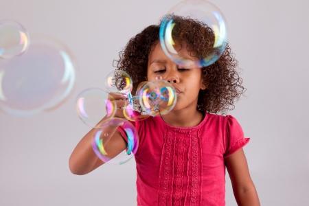 burbujas de jabon: Linda ni�a Afroamericana soplando pompas de jab�n Foto de archivo