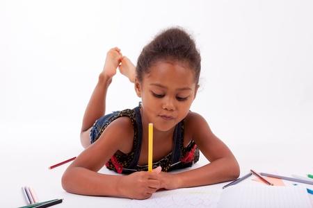niños dibujando: Niña Africana asiática dibujo, acostado en el piso Foto de archivo