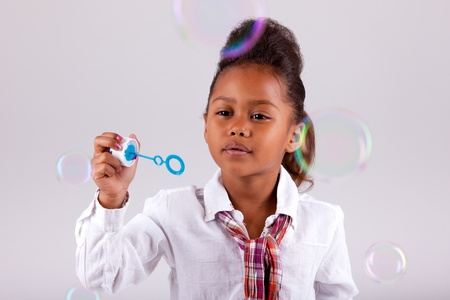 Cute little African American girl blowing soap bubbles photo