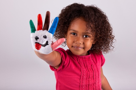 brazilian ethnicity: Little African Asian girl with painted hands in colorful paints Stock Photo