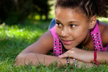 beautiful teen girl: Young african american teenage girl  lying on the grass
