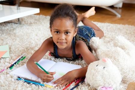 ni�os con l�pices: Ni�a Africana asi�tica dibujo, acostado en el piso Foto de archivo