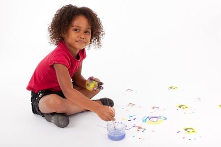 niños pintando: Cute Little pintura africana chica americana en el suelo Foto de archivo