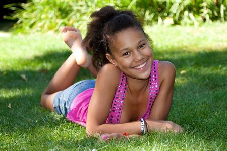 little models: Ni�a adolescente africano americano tirado en el pasto Foto de archivo