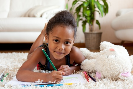 Little African Asian girl drawing, lying down on the floor