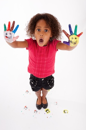 little girl surprised: Little African Asian girl with painted hands in colorful paints Stock Photo
