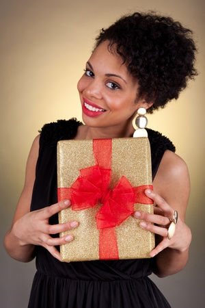 Young African American woman holding a gift box Stock Photo - 11059336