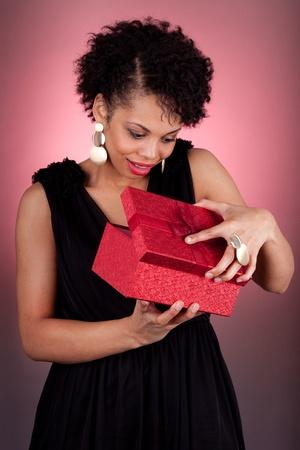 Portrait of a happy young African American woman opening a gift photo