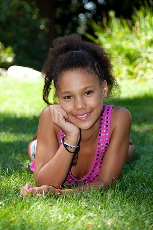 mixed races: Young african american teenage girl  lying on the grass