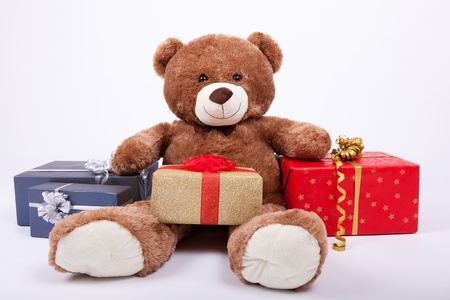 seated: Seated teddy bear with gift boxes, over a white background
