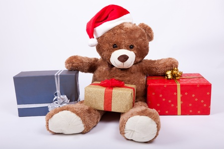 Seated teddy bear wearing a santa hat, over a white background photo