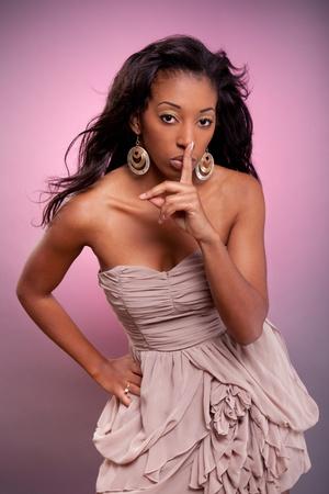 �silence: Joven mujer africana haciendo el gesto de silencio con el dedo