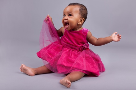 african american infant: Adorable little african american baby girl  sitting on the floor Stock Photo