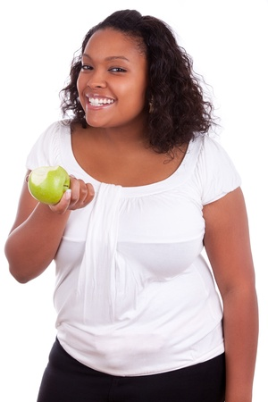 Young african american woman eating an  green apple, isolated on white background photo