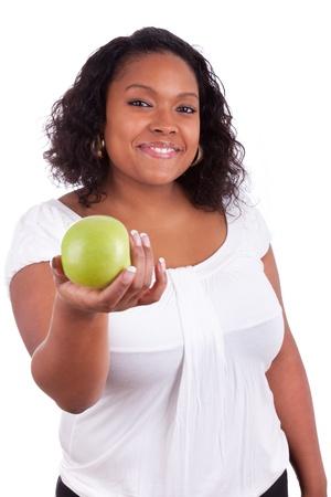 mujeres gordas: Joven mujer afroamericana dando una manzana verde, aisladas sobre fondo blanco Foto de archivo