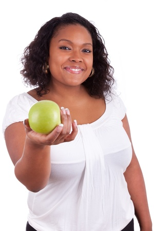 Young african american woman giving an  green apple, isolated on white background photo