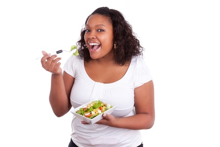 dieting: Young african american woman eating salad, isolated on white background