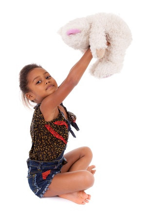 Cute little African Asian girl playing with a teddy bear,  over white background Stock Photo