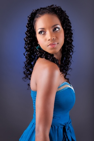 african american woman: Portrait of a young beautiful african american woman in blue dress looking up