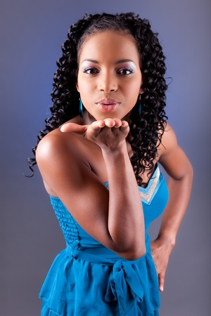 Portrait of a young beautiful african american woman in blue dress blowing a kiss photo