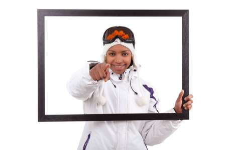 Young smiley woman in ski gears  holding a picture frame, isolated on white background photo