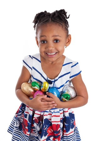 kids eat: Little african american girl holding chocolate easter eggs, isolated on white background