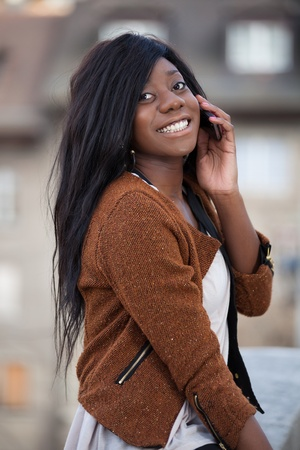 Outdoor of a portrait happy young black  teenage girl using a mobile phone photo