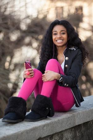 american african: Outdoor di un felice ritratto di giovane ragazza africana adolescente americano l'ascolto di musica